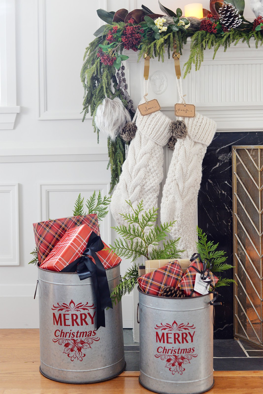 a faux christmas fireplace mantel garland with red seeded eucalyptus, a cedar garland and magnolia leaves. A galvanized bucket holding christmas gifts. Cable knit Christmas stocking