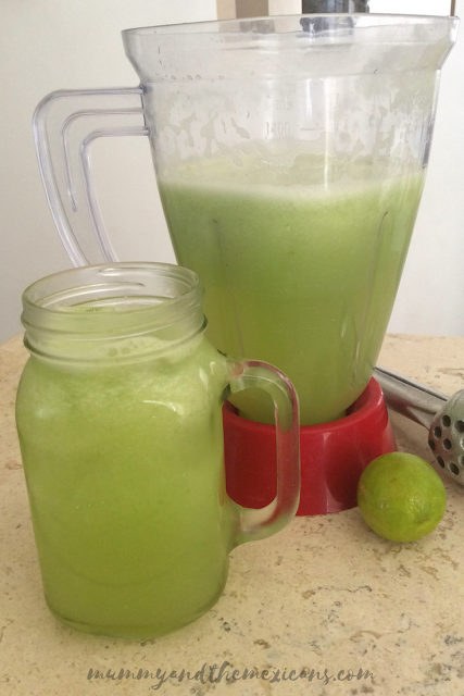 A glass and a jug of cucumber and lime water