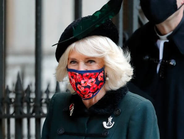 The Duchess of Cornwall wore a green wool coat at Westminster Abbey. The Duchess in a recycled green coat, and a poppy facemask
