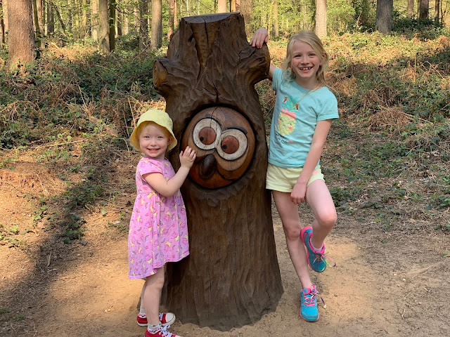 Sisters posing either side of a carving of the owl from Julia Donaldsons gruffalo at Thetford Forest