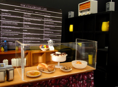 Modern one-twelfth scale miniature cafe counter with various plates of  cakes behind the sneeze guard.