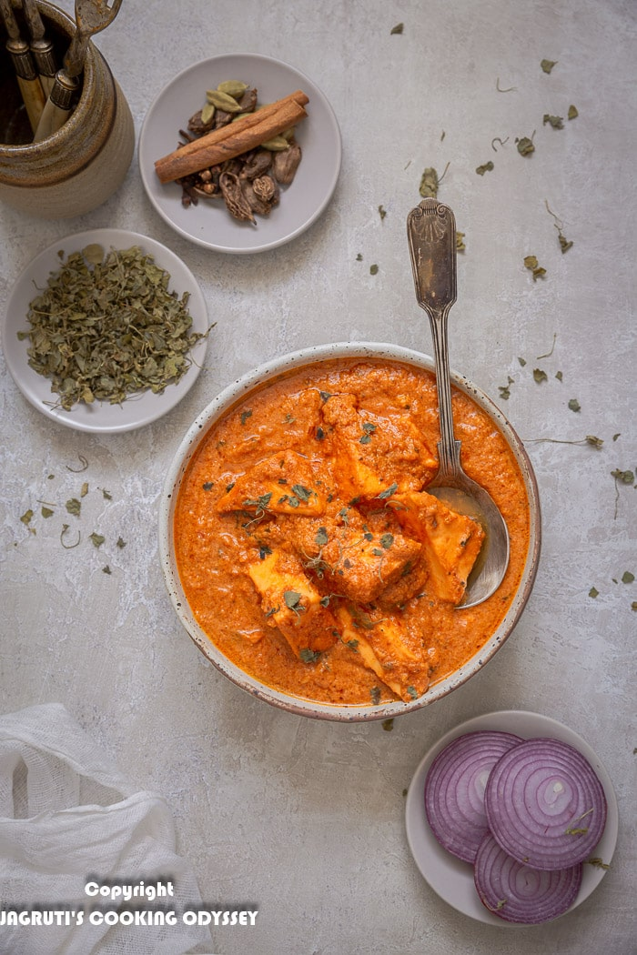 Over the head shot of paneer tikka masala curry in a bowl with spoon