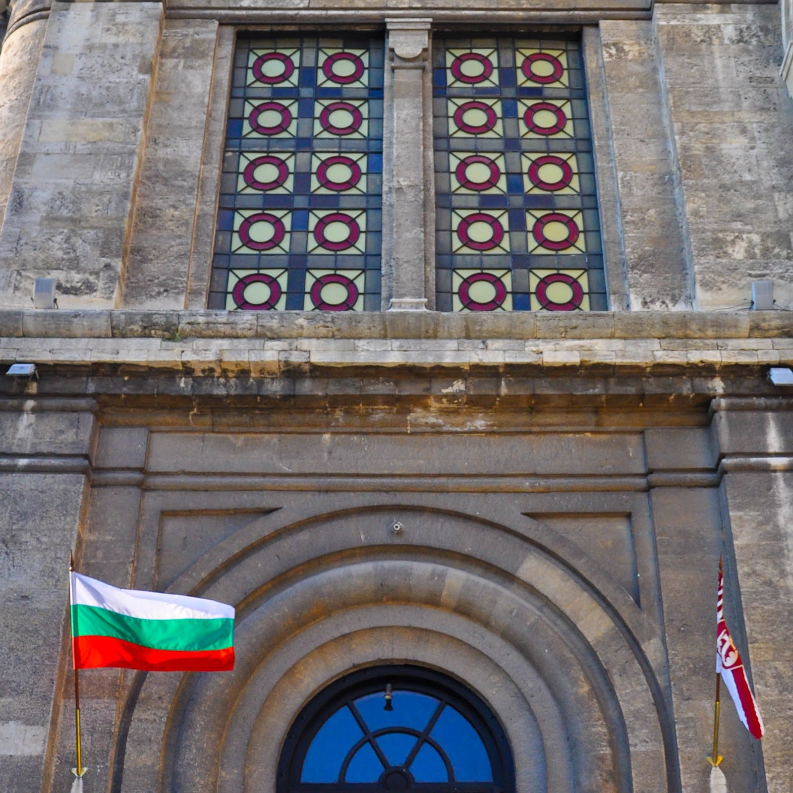 Close-up of the Bulgarian flag and the facade of Dormition of the Mother of God Cathedral, Varna
