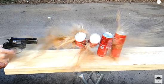 Atirando em latas de coca cola com arma de fogo