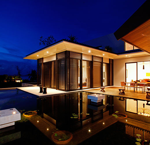 Photo of modern villa at night and the terrace as seen from the pool area