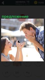 На улице на коленях женщина делает предложение мужчине с кольцом в руках