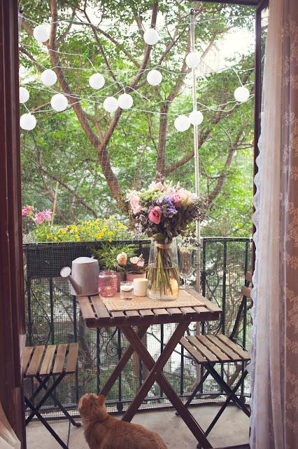 Decoración balcón pequeño gurinalda luz mesa regadera plantas flores
