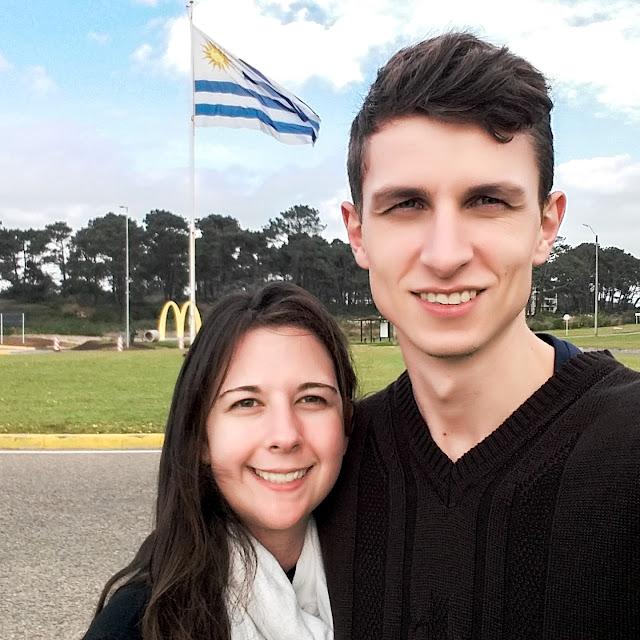 Casal em frente a bandeira do Uruguai