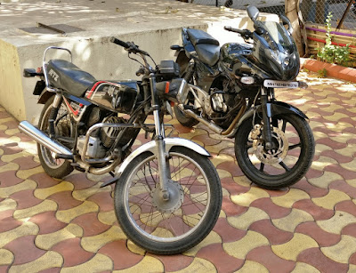 2 bikes parked in a parking lot kawasaki KB100 and bajaj pulsar 220