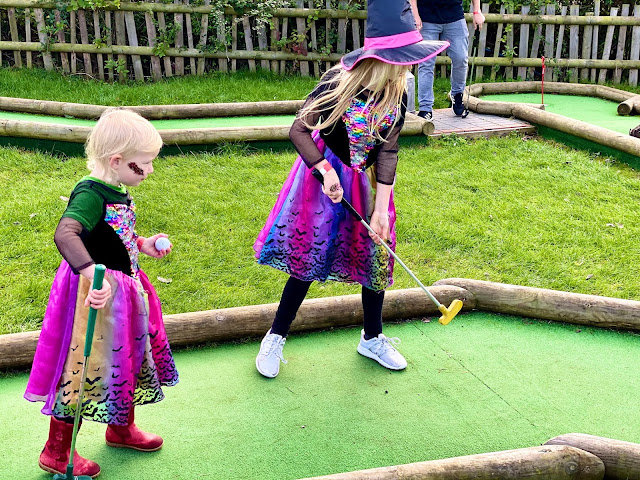two girls dressed as witches playing mini golf