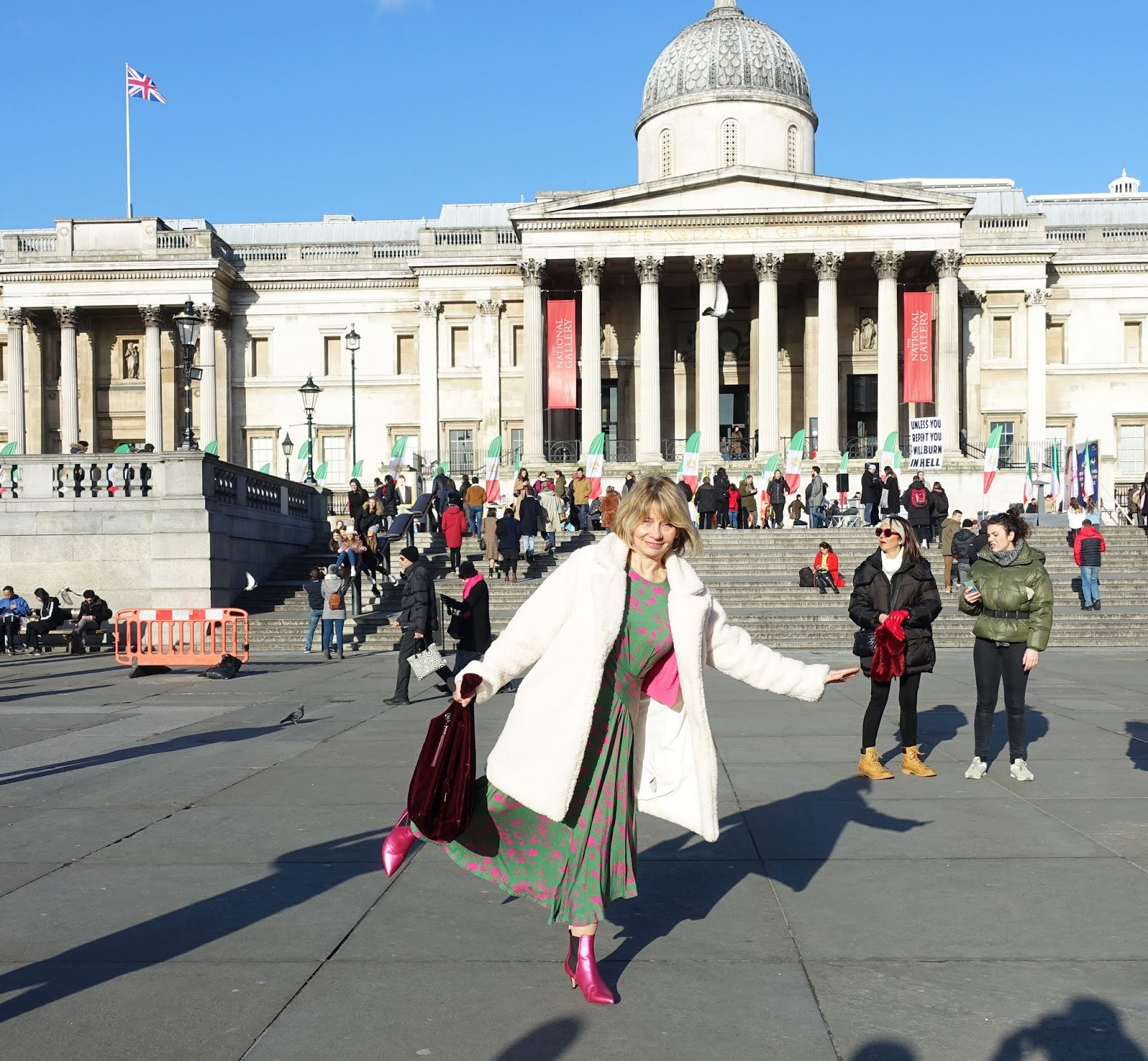 Over 50s blogger Gail Hanlon from Is This Mutton? in pink boots and green and pink dress in Trafalgar Square