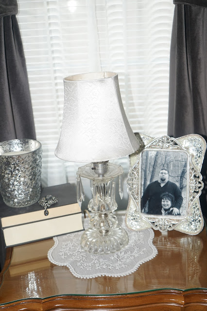 Vintage glass lamp with stacked books, mercury glass candle, picture on nightstand