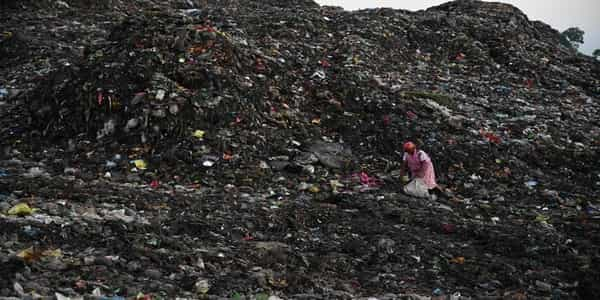 A woman standing in a dumping area.