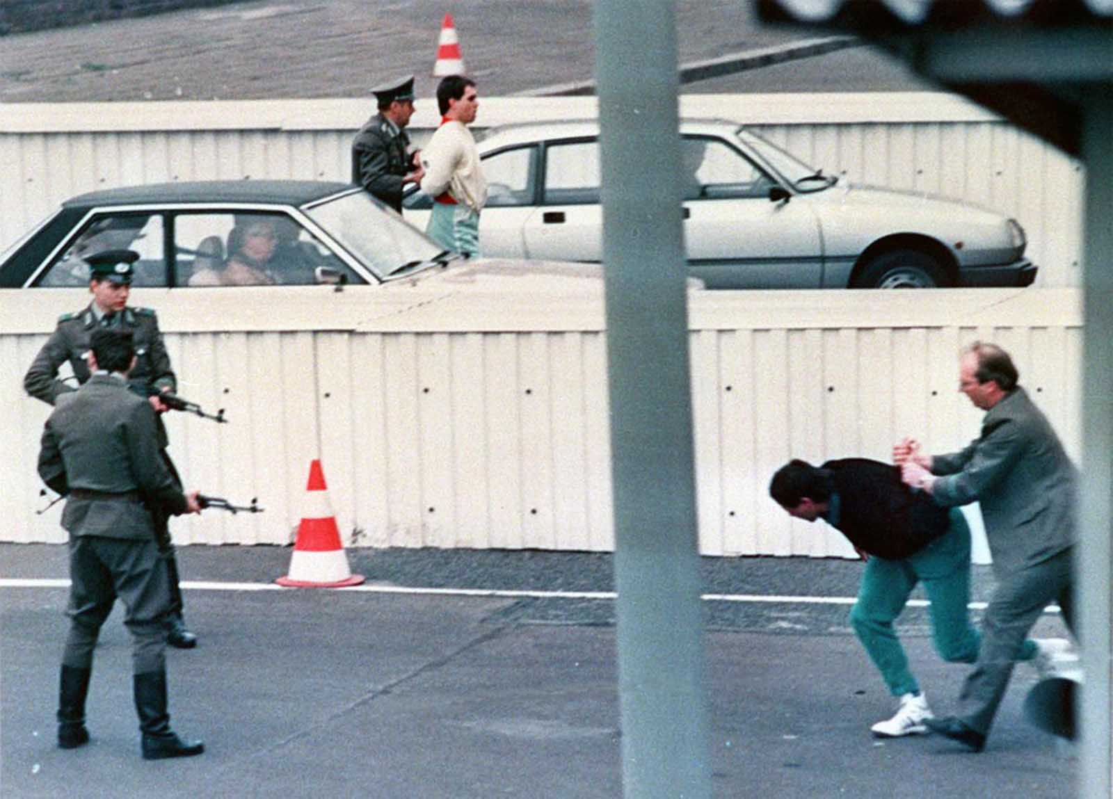 (2 of 3) Two East Berlin refugees are taken away by border guards after a thwarted escape attempt at Berlin border crossing Chausseestreet, in this April 1989 picture.