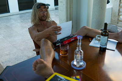 The Beach Bum 2019 movie still where Matthew McConaughey smokes while typing on his typewriter, surrounded by liquor bottles