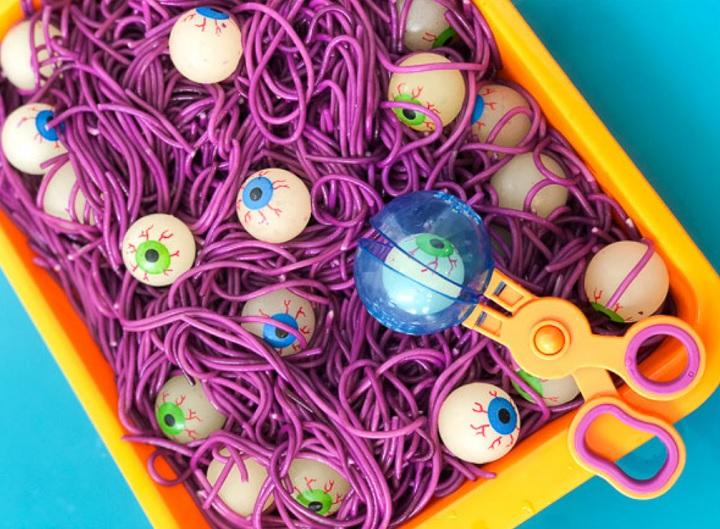 purple spaghetti and eyeballs halloween sensory tray