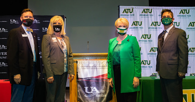 UACCM and ATU personnel standing in front of both both institutions' backdrops.