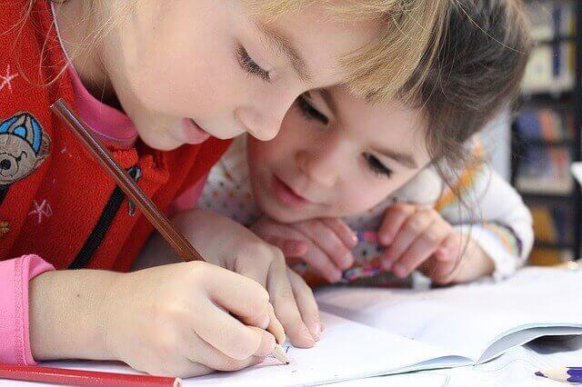 dos niñas escribiendo en la escuela