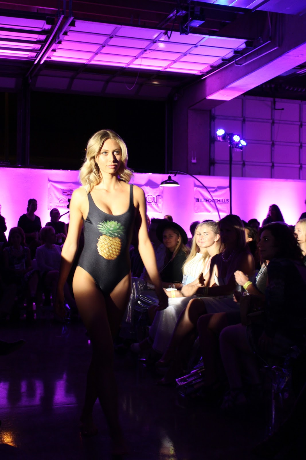 In this photo, the model is rocking a one piece that's black with a pineapple on the front. She commands the runway.