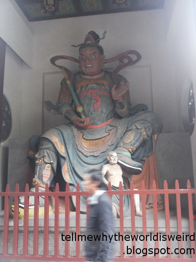 Colorful Buddhist statue. Wild and creepy facial expression.