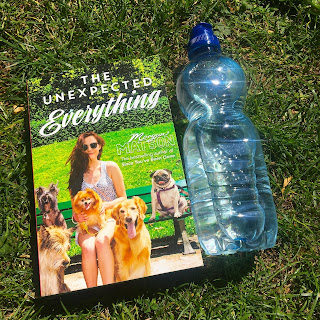 Copy of The Unexpected Everything by Morgan Matson on some grass with a bottle of water to the right
