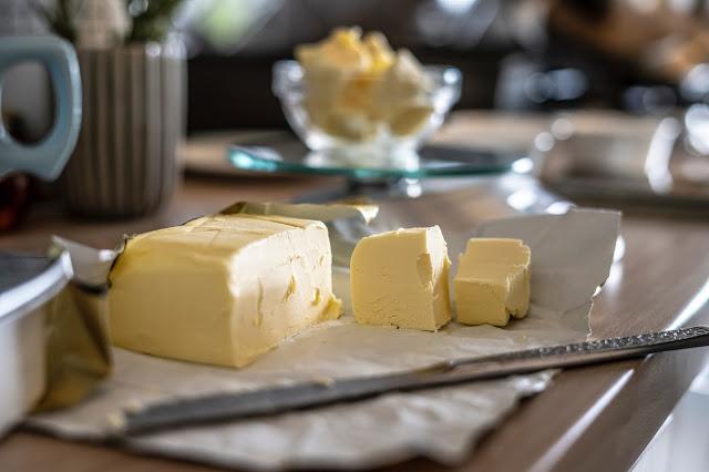 Barra de mantequilla sobre un plato encima de una mesa rodeada por cuchillo, tazas