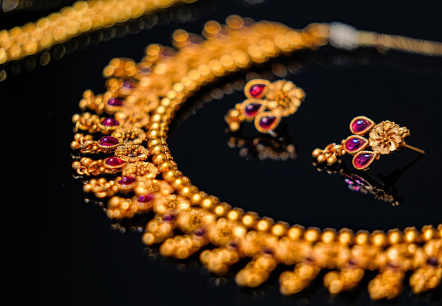 Gold jewelry set displayed on a flat surface.