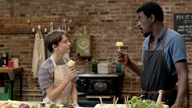 A Black man and white boy cook food together