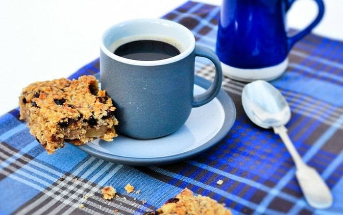 A Scottish Oaty Walnut and Raisin Flapjack sitting on a coffee cup saucer, next to black coffee