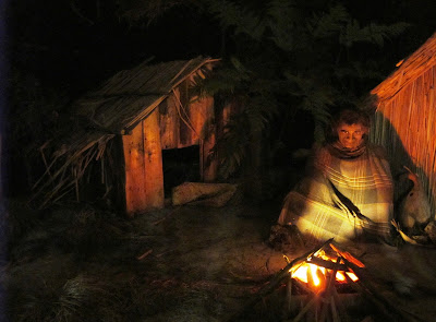 Full-scale model of a 19th century maori village, with a man sitting outside next to a fire, wrapped in a blanket.