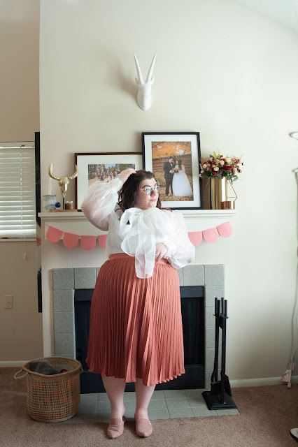 An outfit consisting of a white sheer long sleeve blouse with an attached large sheer bow tucked into a rose pleated midi skirt with dusty pink pointed mules.