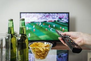 football on TV next to some food and drinks