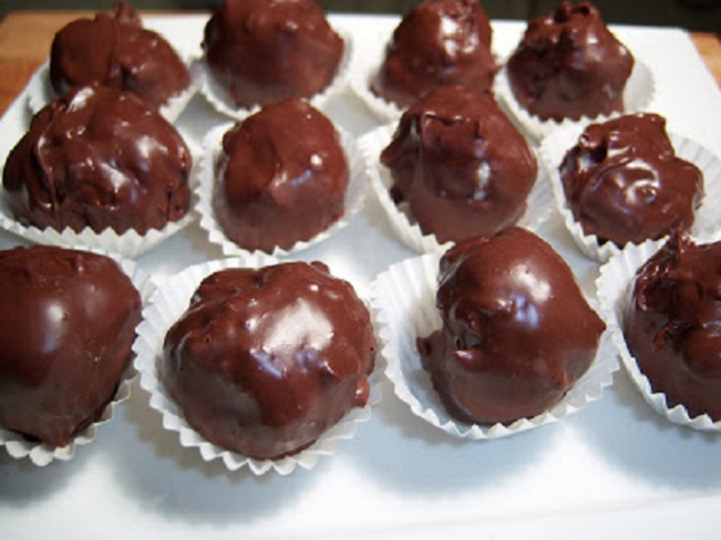 chocolate covered peanut butter balls in paper liners