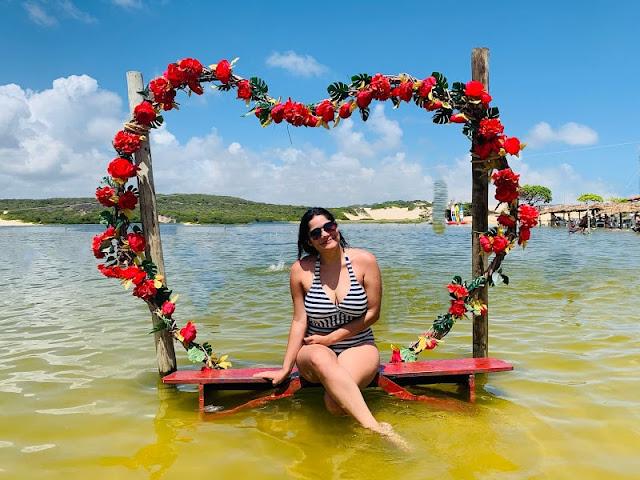 mulher de oculos escuros e cabelo preto mergulhando em uma lagoa esverdeada