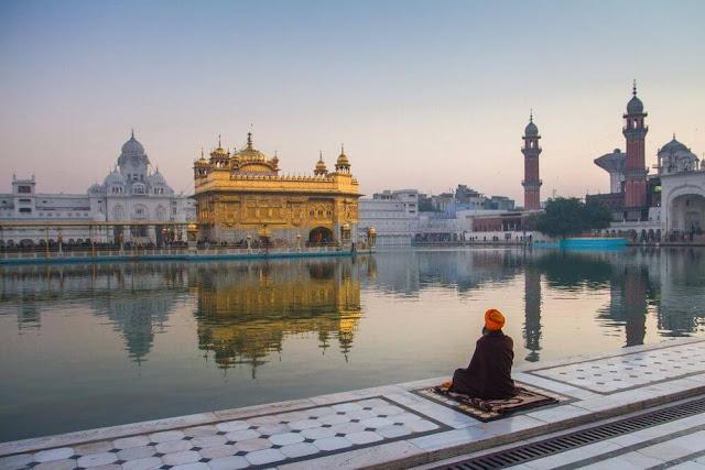 """Tòa nhà linh thiêng nhất trong tôn giáo Sikh, Harmandir Sahib hay còn được gọi là """"Đền Vàng"""", được xây dựng vào thế kỷ 16 để đánh dấu vị trí bên cạnh một hồ nước nơi Đức Phật và Đạo sư Nanak, người sáng lập đạo Sikh, từng thiền định.    Ngôi đền là sự pha trộn tuyệt vời giữa phong cách kiến trúc Ấn Độ giáo và Hồi giáo với điểm nhấn là mái vòm được bao phủ trong 750 kg vàng. Nét ấn tượng của ngôi đền chính là hồ nước được cho có khả năng chữa bệnh, thu hút rất đông người hành hương khắp nơi trên thế giới đến để tắm trong vùng nước linh thiêng."""