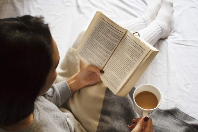 a woman reading a book and holding a cup of coffee