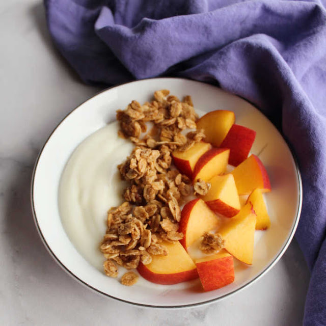 small bowl filled with yogurt, pieces of fresh peach and granola
