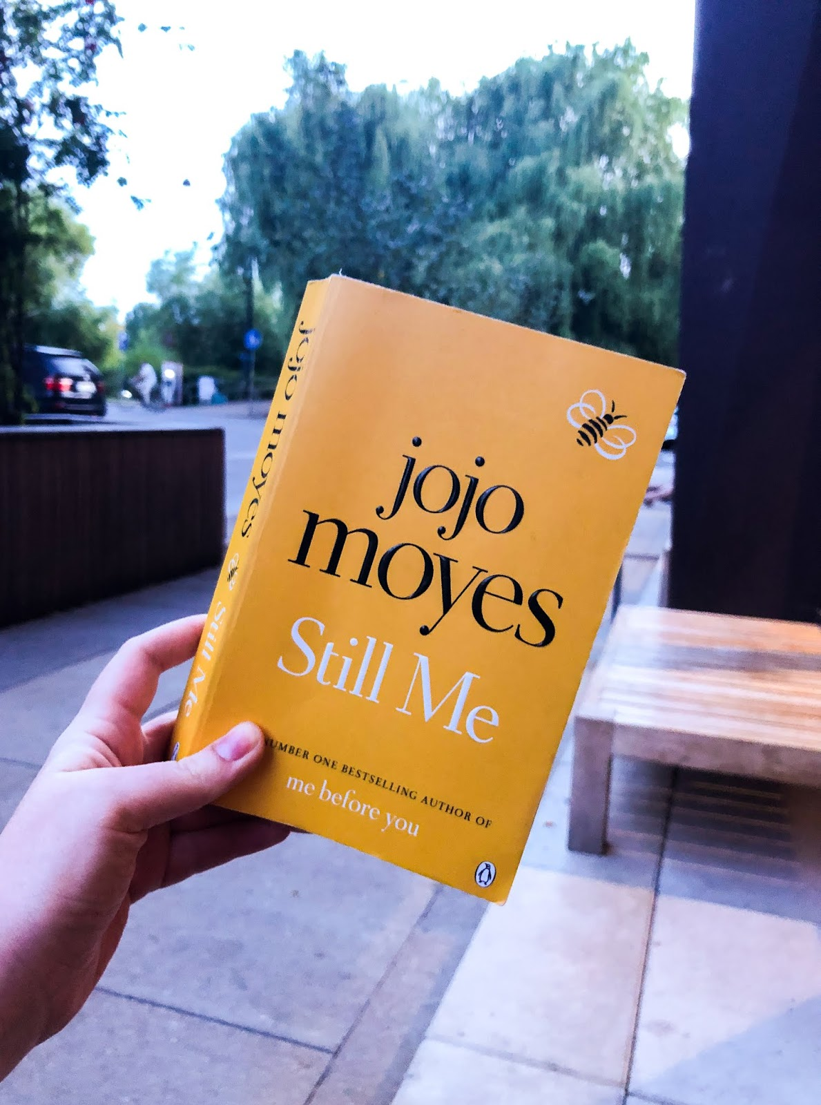 hand holding up jojo moyes' yellow-covered book titled 'still me'