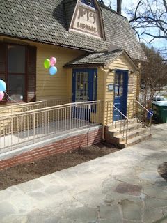 Small building with ramp and balloons tied to railing