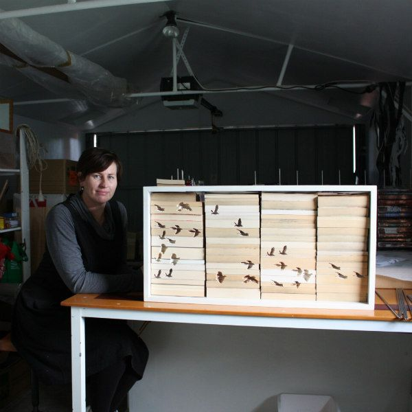 artist with frame filled with paperback books with hand carved design of migrating birds