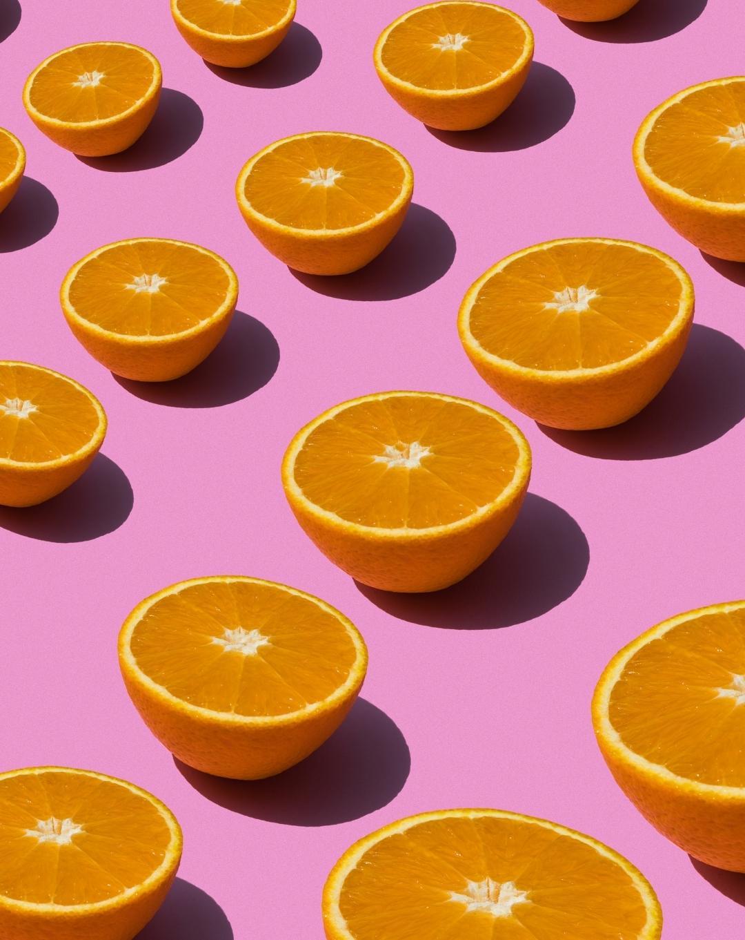 flat lay con naranjas sobre fondo rosa