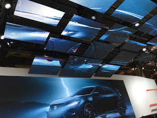 Pic of rows of overhead digital screens on Honda stand