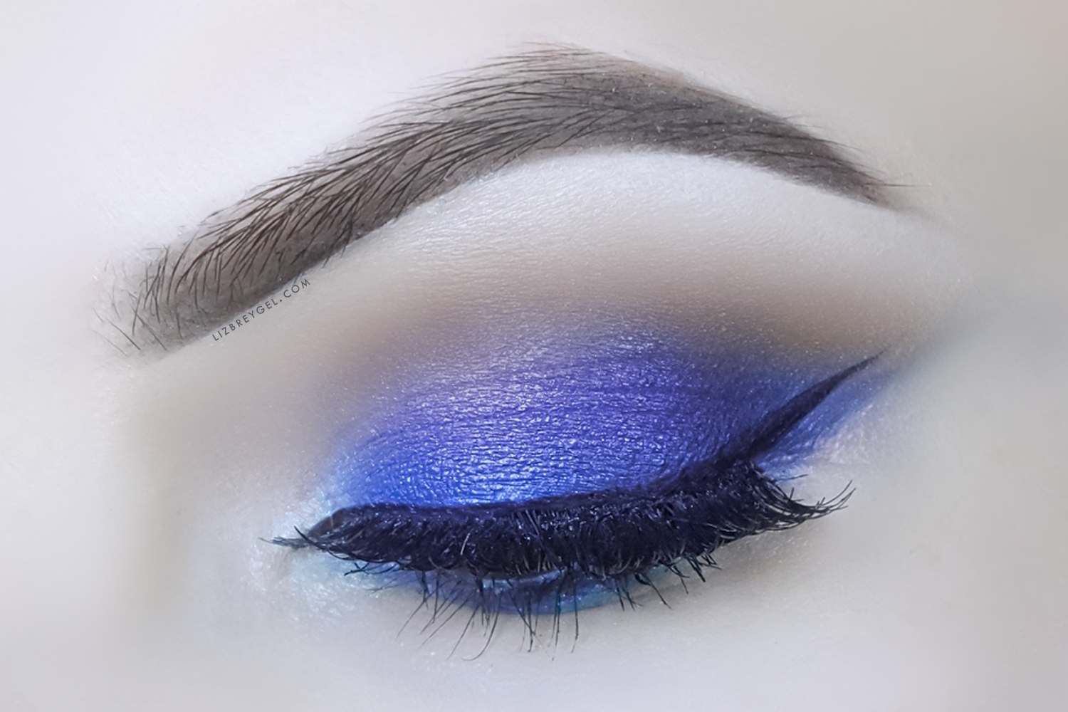 a close up picture of an closed eye with a smokey eye makeup look