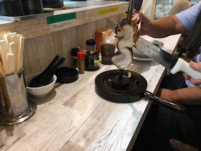 三軒茶屋にある麺GARAGE肉ヲ見ルでシュラスコを客が箸でキャッチしているところ