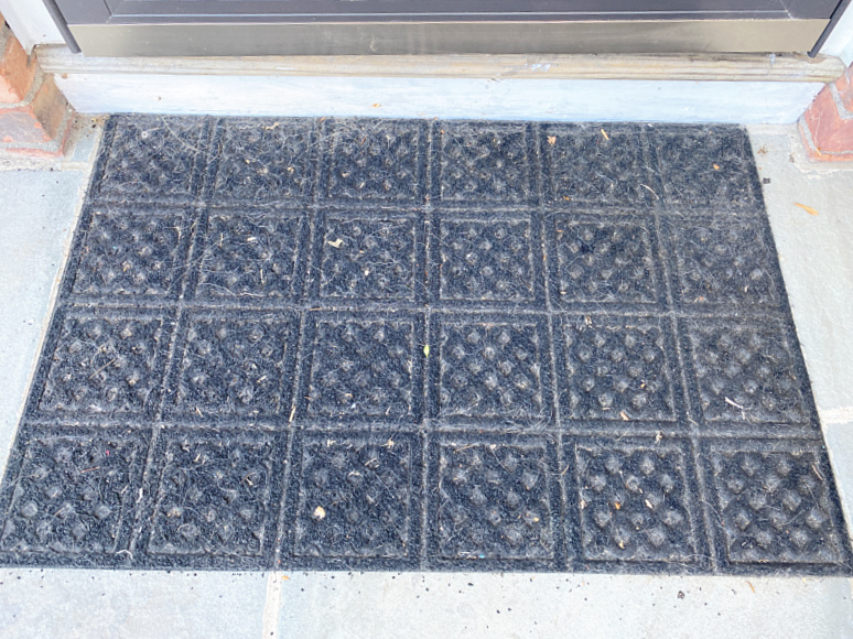 old outdoor mat with black pieces falling off