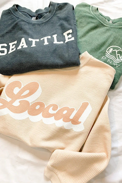 Local Seattle sweatshirts laid out on a white background