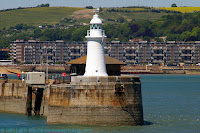 Prince of Wales Pier Light was built 1902. 46 feet high stone tower. Very quick flashing green light VQ, 100+ flashes per minute. Cafe behind lighthouse. Gateway Flats on seafront. Taken from above Cruise Terminal 3, Admiralty Pier, Dover Western Docks Revival.