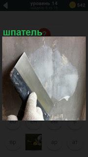 шпателем производят штукатурку стены