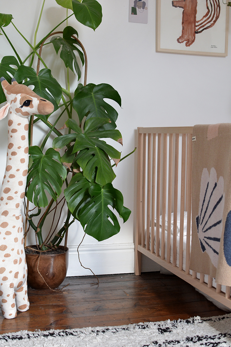 wooden cot and neutral nursery decor