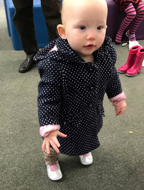 A baby girl standing in a navy coat with white spots trying on a pair of silver first shoes from Clarks